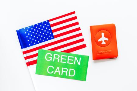Tarjetas de residente permanente de los Estados Unidos de América. Concepto de inmigración. Texto tarjeta verde cerca de la cubierta del pasaporte y vista superior de la bandera de EE. UU. Sobre fondo blanco