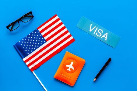 Visa to United States of America concept. Text visa near passport cover and USA flag on blue background top view
