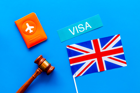 Visa to Britain concept. Text visa near passport cover and british flag, hammer on blue background top view Banco de Imagens