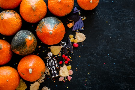 Preparing to Halloween. Pumpkins and cute figures of halloween evils. Skeleton, witch. black background top view copy space Stock Photo