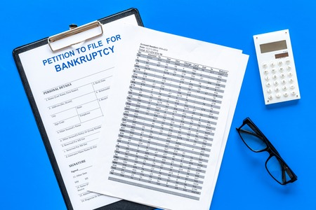 Petition to file for bankruptcy. Empty form ready to fill near calculator on blue background top view