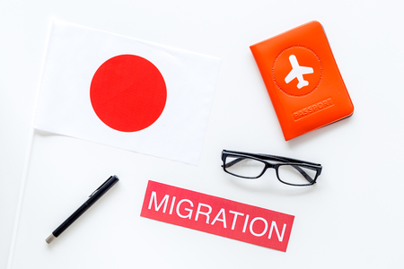 Immigration to Japan concept. Text immigration near passport cover and japanese flag on white background top view Stock Photo