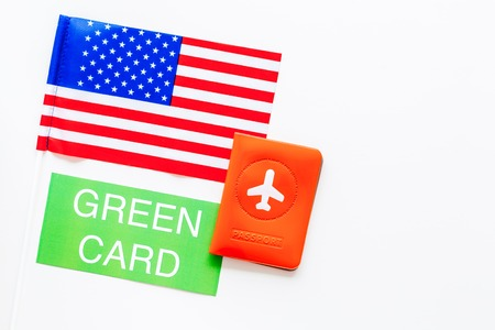 United States of America permanent resident cards. Immigration concept. Text green card near passport cover and US flag top view on white background space for text