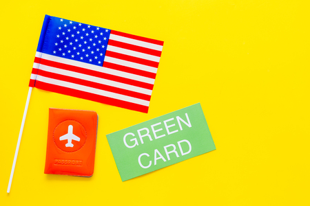 United States of America permanent resident cards. Immigration concept. Text green card near passport cover and US flag top view on yellow background copy space Фото со стока