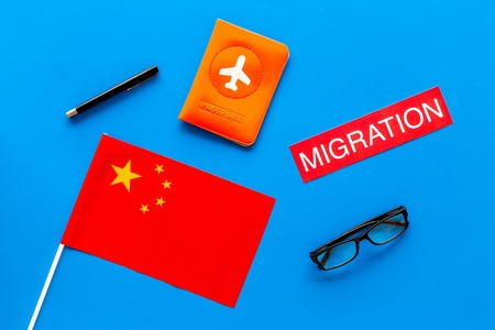 Immigration to China concept. Text innigration near passport cover and chinese flag on blue background top view