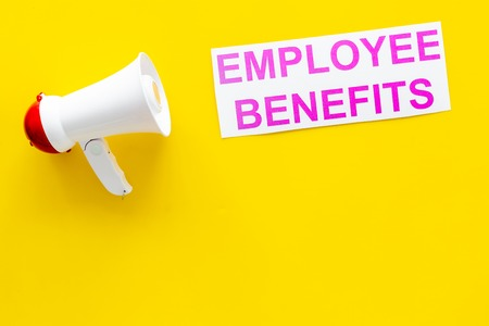 job with social guarantees. Printed words empoyee benefits near megaphone on yellow background with computer keyboard top view copy space