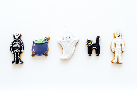 Halloween traditions. Halloween gingerbread in shape of evil characters on white background top view copy space