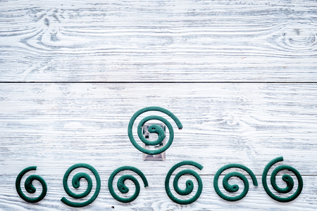 Mosquito repellent for outdoor: garden, summer house, picnic. Green spiral on grey wooden background top view copy space pattern Archivio Fotografico - 109207757