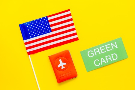 United States of America permanent resident cards. Immigration concept. Text green card near passport cover and US flag top view on yellow background copy space Stock Photo