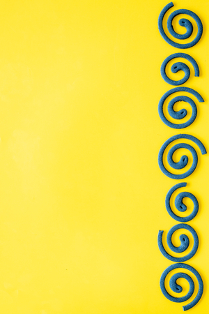 Mosquito repellent for outdoor. Green spiral on yellow background top view copy space pattern