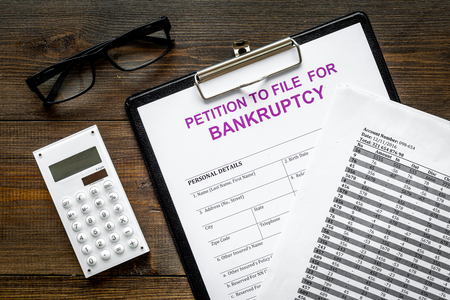 Petition to file for bankruptcy. Empty form ready to fill near calculator on dark wooden background top view Stockfoto