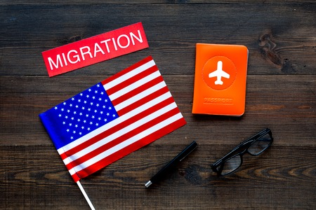 Immigration to United States of America concept. Text immigration near passport cover and USA flag on dark wooden background top view
