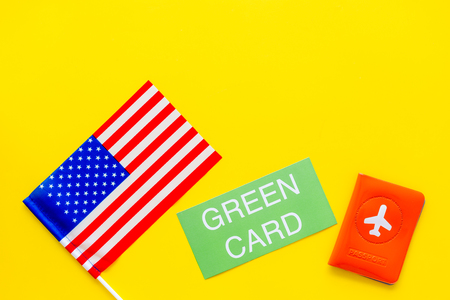 United States of America permanent resident cards. Immigration concept. Text green card near passport cover and US flag top view on yellow background copy space 版權商用圖片