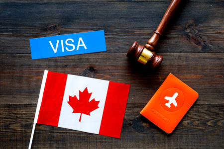 Visa to Canada concept. Text visa near passport cover and canadian flag, hammer on dark wooden background top view
