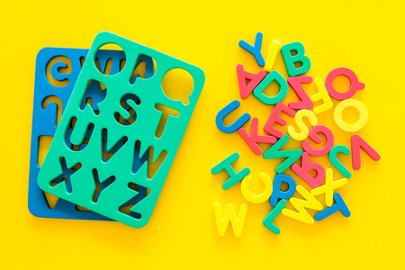 Foam alphabet for kids concept. English letters in disorder near stencil on yellow background top view