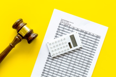 Declare bankruptcy concept. Judge gavel, financial documents, calculator on yellow background top view