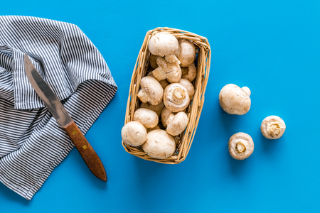 Collect mushroom champignons. Fresh raw whole champignons in basket near knife on blue background top view