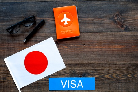 Immigration to Japan concept. Text immigration near passport cover and japanese flag on dark wooden background, top view space for text Фото со стока