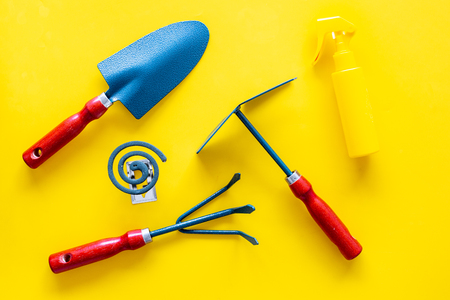 Mosquito protection for garden. Mosquito coil and spray near garden tools on yellow background top view Stock fotó