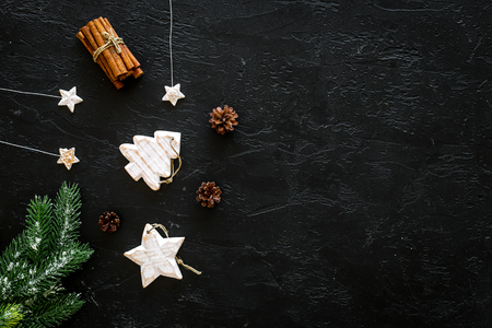 Spruce branch, cones and vintage toys in shape of spruce and stars on black background for decoration on chrismas or new year top view copy space Stock Photo