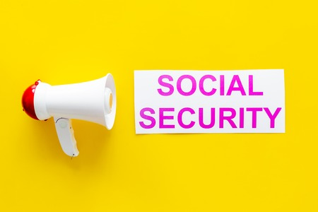Printed words social security near megaphone on yellow background with computer keyboard top view space for text