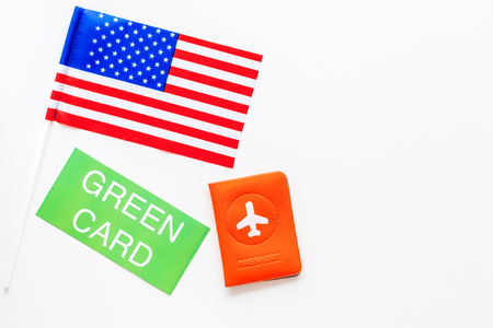 United States of America permanent resident cards. Immigration concept. Text green card near passport cover and US flag top view on white background copy space Фото со стока