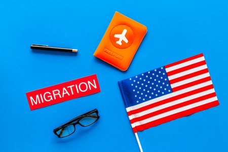 Immigration to United States of America concept. Textimmigration near passport cover and USA flag on blue background top view.