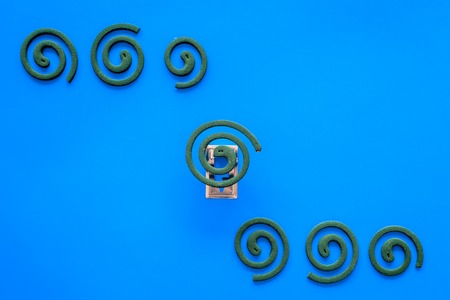 Mosquito repellent for outdoor: garden, summer house, picnic. Green spiral on blue background top view.