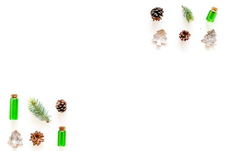 New Year composition with pine sprigs, cones, spruce figure, fir oil on white background top view.