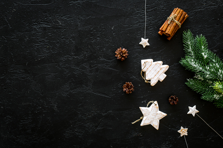Spruce branch, cones and vintage toys in shape of spruce and stars on black background for decoration on chrismas or new year top view. Stock Photo