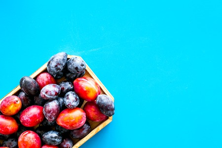 Plums on dinning table. Fresh raw red and blue plum in wooden tray on blue background top view.