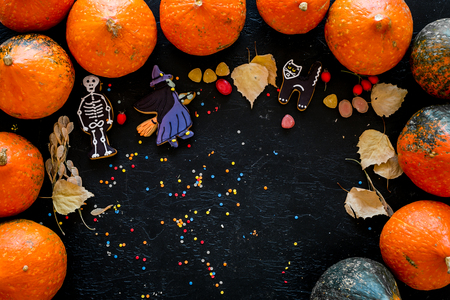 Preparing to Halloween. Pumpkins and cute figures of halloween evils. Skeleton, witch. black background top view.