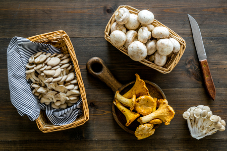 Collect mushroom concept. Champignons, oysters, chanterelles in basket near knife on dark wooden background top view. Reklamní fotografie