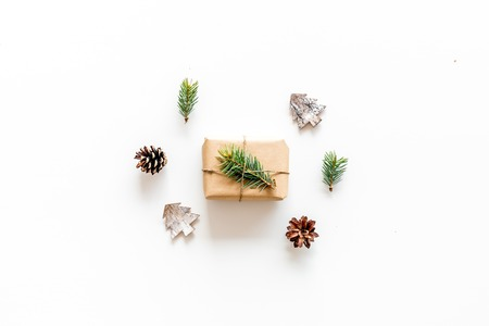 Composition with New Year gift wrapped in craft paper and decorted with pine sprout near pine sprigs, cones, spruce figure, fir oil on white background top view. Stock fotó