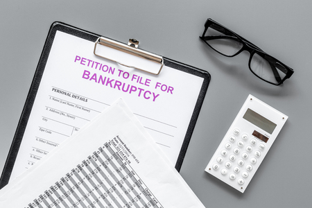 Petition to file for bankruptcy. Empty form ready to fill near calculator on grey background top view.