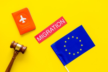 Immigration to Europe concept. Text immigration near passport cover and flag.