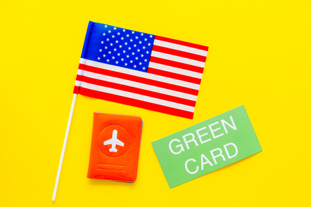 United States of America permanent resident cards. Immigration concept. Text green card near passport cover and US flag top view on yellow background.