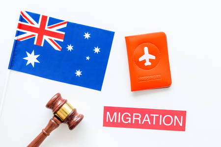 Immigration to Australia concept. Text immigration near passport cover and australian flag, hammer on white background top view Reklamní fotografie