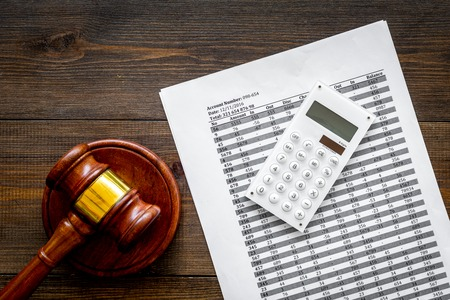 Declare bankruptcy concept. Judge gavel, financial documents, calculator on dark wooden background top view space for text
