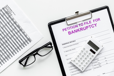 Petition to file for bankruptcy. personal bankruptcy. Empty form ready to fill near calculator on white background top view
