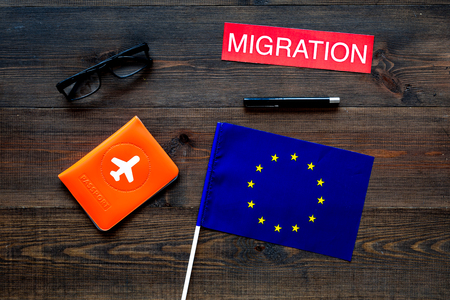 Immigration to Europe concept. Text immigration near passport cover and european flag on dark wooden background top view