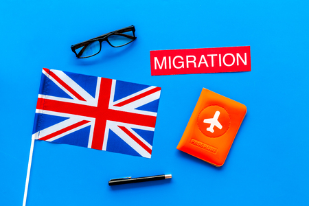 Immigration to Britain concept. Text immigration near passport cover and british flag on blue background top view