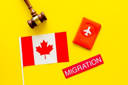 Immigration to Canada concept. Text immigration near passport cover and canadian flag, hammer on yellow background top view