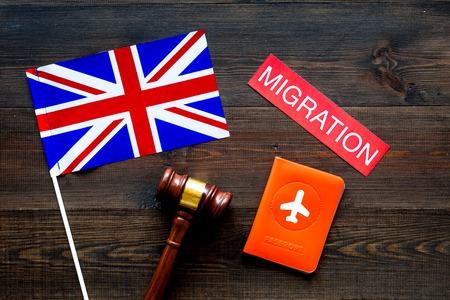 Immigration to Britain concept. Text immigration near passport cover and british flag, hammer on dark wooden background top view