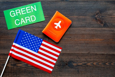 Green card text near passport cover and USA flag top view on dark wooden background copy space. Immigration to United states of america Фото со стока