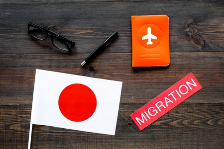 Immigration to Japan concept. Text immigration near passport cover and japanese flag on dark wooden background top view Фото со стока