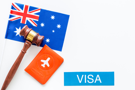 Visa to Australia concept. Text visa near passport cover and australian flag, hammer on white background top view copy space