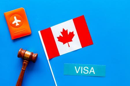 Visa to Canada concept. Text visa near passport cover and canadian flag, hammer on blue background top view