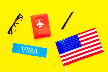 Visa to United States of America concept. Text visa near passport cover and USA flag on yellow background top view