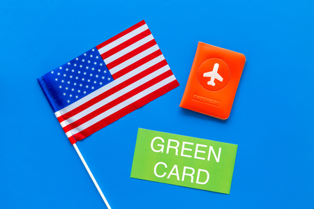 Green card text near passport cover and USA flag top view on blue background Immigration to United states of america Stock Photo